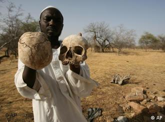 Sudanese Darfur survivor Ibrahim holds human skulls at the site of a mass grave on the outskirts of the West Darfur town of Mukjar, Sudan, April 23, 2007. The human bones and skulls are hard to hide in this corner of Darfur: They lie just a few inches below the surface in a mass grave here. Some bones poke above the dirt, surrounded by half-buried, rotting clothes. (AP Photo/Nasser Nasser)