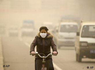 A cyclist wearing a face mask cycles through smog