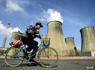 Chinese man cycles past coal burning power plants