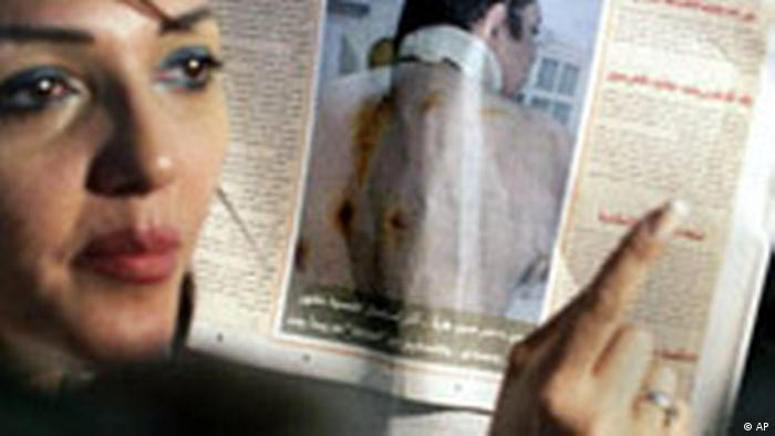 Gamila Ismail, wife of prominent jailed dissident Ayman Nour, who came distant second to President Hosni Mubarak in the 2005 presidential elections, and who is serving a five-year prison sentence after being convicted of fraud, displays a picture of him on the front page of his party newspaper, Al Ghad, showing what she said were several injuries from bad treatment inside his prison for her husband at a Cairo court Thursday, May 31, 2007. A court has turned down a request to review a jail sentence on Egypt's leading opposition prisoner on grounds of poor health . Ismail has been critical of the Bush administration and accused it of turning a blind eye to her husband's case in favor of winning Mubarak's support for U.S. policies in the region. (AP Photo/Amr Nabil)