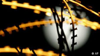 A full moon rises behind a barbed wire fence