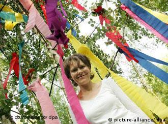 Eine Frau steht unter einem Maibaum