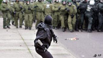 Ein vermummter Demonstrant wirft einen Stein nach einer Polizeikette, Quelle: AP