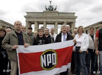 NPD supporters hold an NPD flag in front of Brandenburg Gate in Berlin