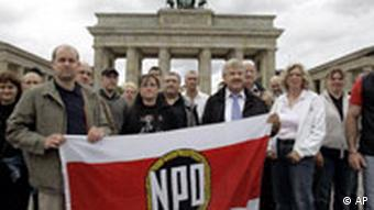 Udo Voigt, third from right, Chairman of the German right wing party NPD, poses with followers and a party flag in front of the Brandenburg gate in Berlin