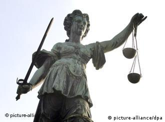 A statue of Justice holding balanced scales and a sword