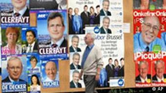 An unknown man passes in front of various posters advertising Belgian political parties