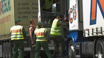 Drei Grenzpolizisten besteigen einen LKW