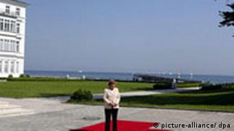 German Chancellor Angela Merkel stands on a red carpet