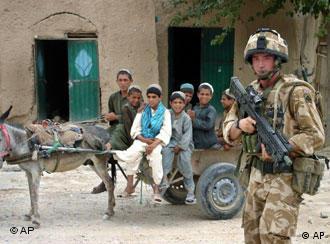 Ein bewaffneter Soldat steht in einem Dorf, im Hintergrund Kinder mit einem Eselskarren. Foto: AP