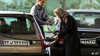 A woman and man at a gas station in Tehran