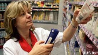 A woman puts goods on a shop shelf
