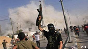 A Palestinian militant from Hamas celebrates as the Preventive Security headquarters is blown up in the background after it was captured in fighting from Fatah loyalist security forces in Rafah, in the southern Gaza Strip, Thursday, June 14, 2007.