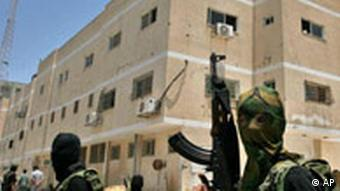 Palestinian militants from Hamas stand in front of the preventive security headquarters after they captured it from Fatah loyalist security forces in Gaza City, Thursday, June 14, 2007.