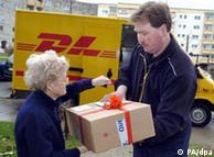 Una señora recibe un paquete de Quelle con el correo