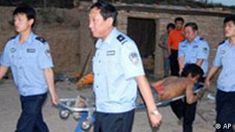 An injured slave laborer with back injury is carried out by Chinese police officers on a stretcher after authorities raided a brick kiln in Hongtong County of Linfen, in China's northern Shanxi Province, on May 27, 2007. Chinese authorities raided illegal brick kilns and coal mines Saturday, June 16, 2007 to rescue hundreds of laborers and child workers kept and made to work in slavery conditions. (AP Photo/EyePress) **CHINA OUT**