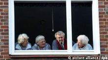 Vom Fenster aus beobachten ältere Leute am Samstag (29.03.2004) eine Demonstration in Hamburg. Foto: Kay Nietfeld dpa/lno