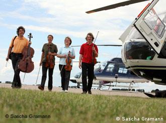 Four musicians holding string instruments march past helicopters