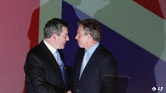 Gordon Brown, left, and Tony Blair shake hands in front of a Union Jack