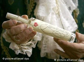 A historical bottle of Original Eau de Cologne is held by a man dressed in 18th century clothes