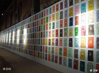 Eine Wand mit vielen, kleinen, bunten Gesichtern, Foto: DW