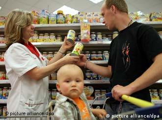 Die Mitarbeiterin Karin Jacobs vom Drogeriemarkt Rossmann in Frankfurt (Oder) berät einen Kunden mit Kleinkind beim Kauf von Babynahrung aufgenommen am 23.05.2007 (Illustrationsfoto zum Thema Frauen im Beruf). Foto: Patrick Pleul +++(c) dpa - Report+++