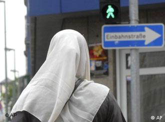 A Muslim woman with a headscarf crossing the road