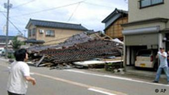 Residents stand near a house collapsed by a strong earthquake in Kashiwazaki, northwestern Japan, Monday, July 16, 2007.