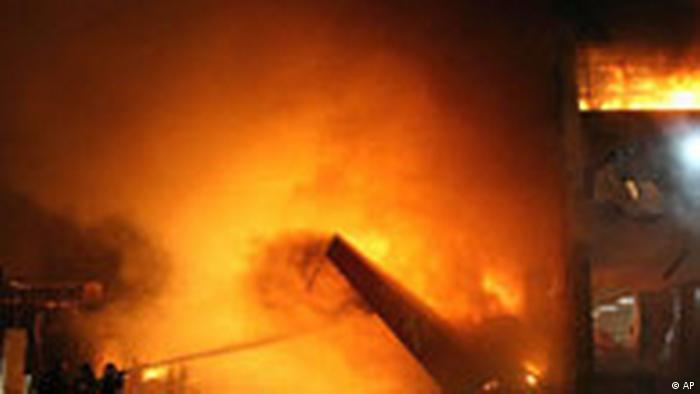 A foto mostra muito fogo e bombeiros tentam apagar as chamas provocadas pelo acidente