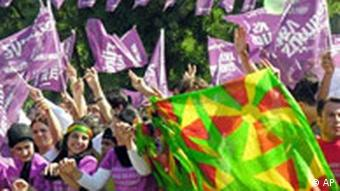Turkish Kurds dance during an rally. Women wave colourful banners and flags
