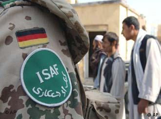 ISAF soldier with German flag on his jacket stands in front of Afghan men