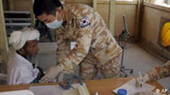 A South Korean medic examines an Afghan patient