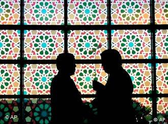 Two backlit people talking in front of a stained glass window in Libya