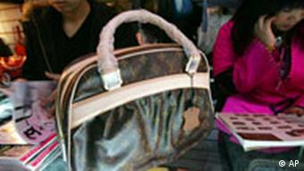 A shop assistant displays a fake Louis Vuitton bag at a store in Beijing Wednesday (AP Photo/Greg Baker)