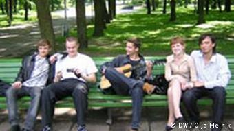 Молодые люди с гитарой сидят на скамейке в парке