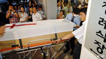 Workers carry a coffin containing the body of slain South Korean Bae Hyung-kyu, from an ambulance in Anyang, west of Seoul, South Korea, Monday, July 30, 2007. The body of the South Korean pastor shot dead by his Taliban captors in Afghanistan arrived back in South Korea on Monday, as the families of the remaining 22 South Korean hostages pleaded for their loved ones' release. The Korean read Funeral parlor. (AP Photo/Korea Pool) **KOREA OUT**