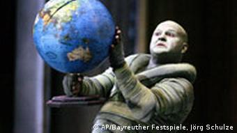 Man holds globe in the opera Siegfried