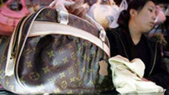 A shop assistant displays a fake Louis Vuitton bag at a store in Beijing