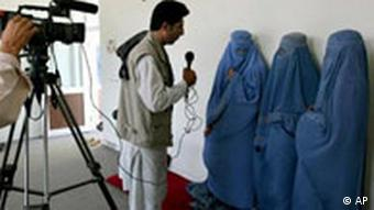 Three Afghan women in Burqas talk to a television crew
