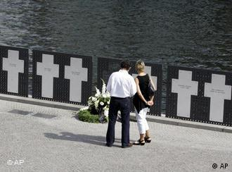 Tourists look at the remembrance crosses for the victims of the Berlin wall on Monday, Aug. 13, 2007 in Berlin.