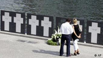 Tourists look at white crosses for those killed while trying to cross the Berlin wall