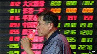 A Chinese investor walks past the stock price monitor at a private security company