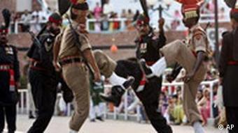 Indian Border Security Force soldiers, in brown uniform, and Pakistani Rangers soldiers, in black uniform, at Wagah border