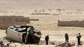 ISAF soldiers investigate the scene of an explosion that killed three German police officers