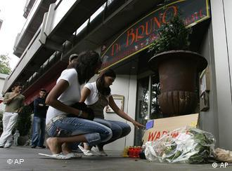 Young people lay flowers at the site of the shootings