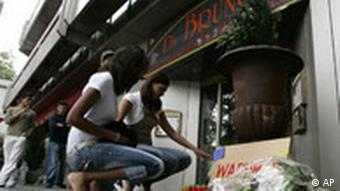 People laying flowers outside the Da Bruno restaurant in Duisburg where six men were shot