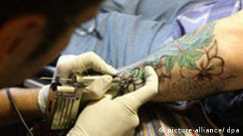 A tattoo artists works on the arm of a customer