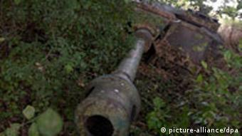 The rusty barrel of a tank's gun peeks out from under bushes