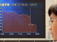 Un peaton mira una pantalla que muestra la caída libre del índice Nikkei japonés, que perdió más de 300 puntos en la jornada de este jueves.