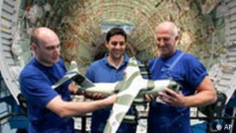 Three Airbus workers hold a scale model of a A400M while standing in front the first fuselage of this military type at the Airbus manufacturing site in Bremen, northern Germany